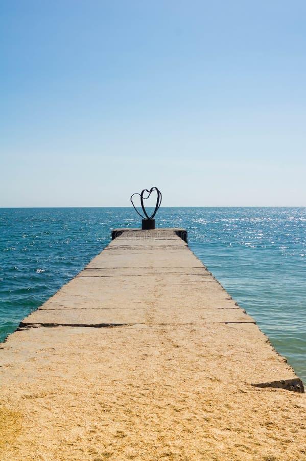 Mooie romantische liefdeachtergrond, silhouet van hartelijk paar op de pijler bij zonsondergang royalty-vrije stock foto