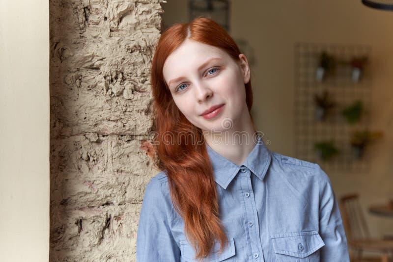 Mooie roodharige jonge vrouw dichtbij het venster royalty-vrije stock afbeeldingen