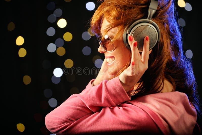Mooie roodharige met hoofdtelefoons royalty-vrije stock foto's