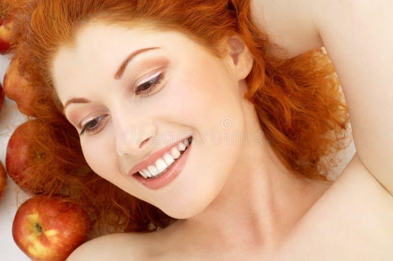 Mooie roodharige met rode appelen stock foto