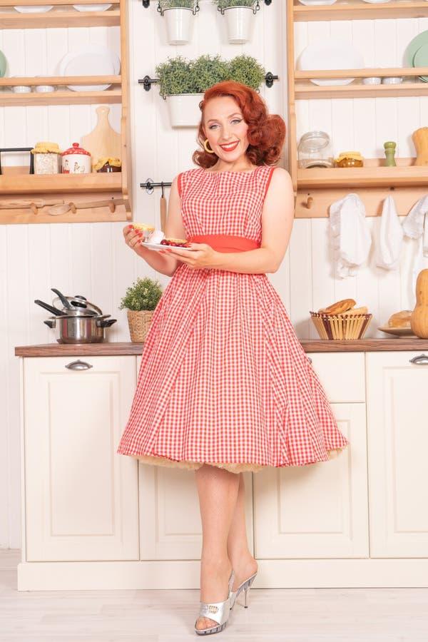 Mooie roodharige pinup die gelukkig meisje het stellen in een retro rode kleding in de alleen keuken glimlachen royalty-vrije stock foto's