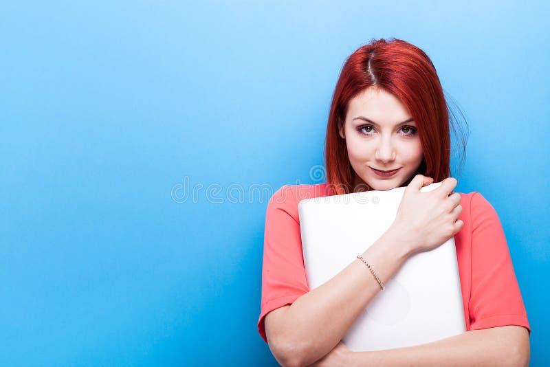 Mooie roodharigestudente die laptop in haar wapens houdt royalty-vrije stock afbeelding