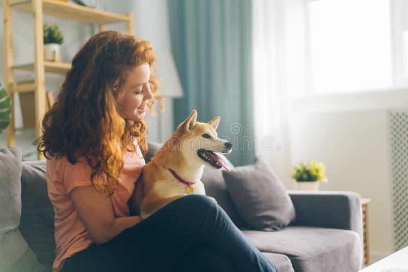Mooie roodharigevrouw die zitting van een hond op laag in flat het glimlachen koesteren royalty-vrije stock fotografie