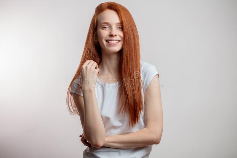 Mooie roodharigevrouw met lang haar over witte achtergrond stock afbeelding