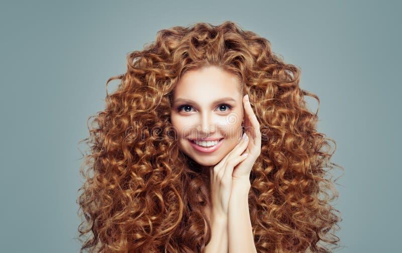 Mooie roodharigevrouw met lang krullend die haar op wit wordt geïsoleerd Haircareconcept stock afbeeldingen