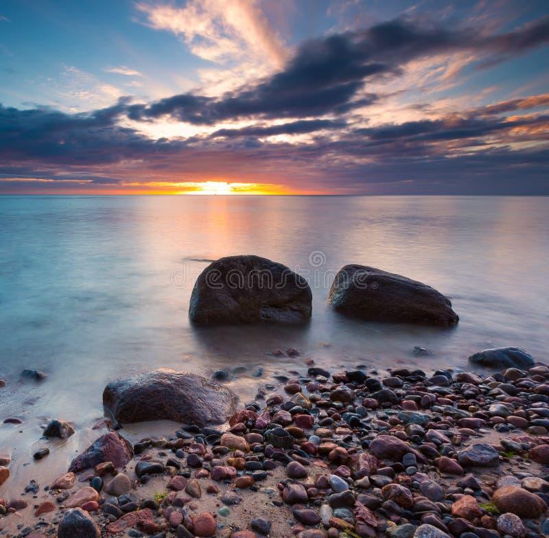 Mooie rotsachtige overzeese kust bij zonsopgang of zonsondergang royalty-vrije stock afbeelding