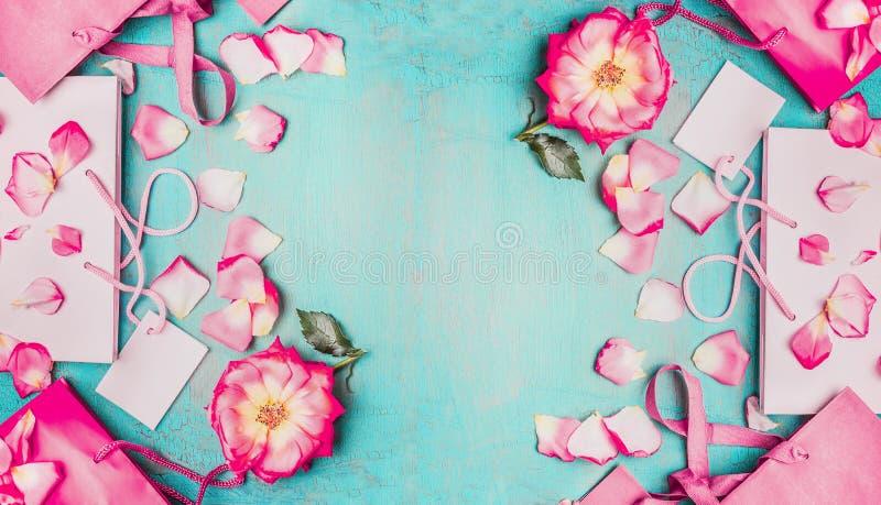 Mooie roze bloemen met bloemblaadjes en roze document het winkelen zakken op lichtblauwe achtergrond, hoogste mening, banner royalty-vrije stock foto