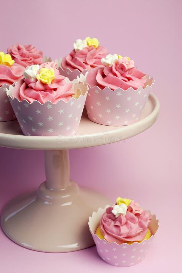 Mooie roze cupcakes in sterhouders op roze caketribune stock fotografie