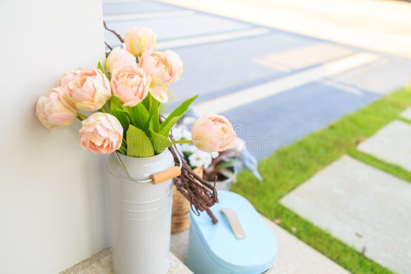 Mooie roze kunstbloemen in witte vaas op een vloer stock afbeeldingen