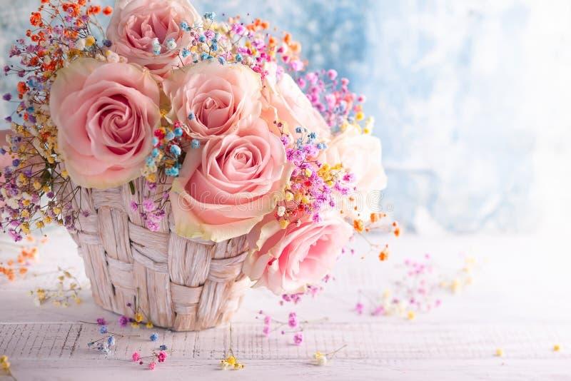 Mooie roze rozen voor vakantie in mand op lijst stock fotografie