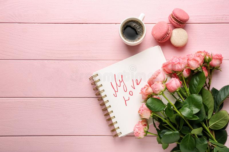 Mooie rozen, kop van koffie, makarons en notitieboekje op houten lijst De Viering van de valentijnskaartendag stock foto