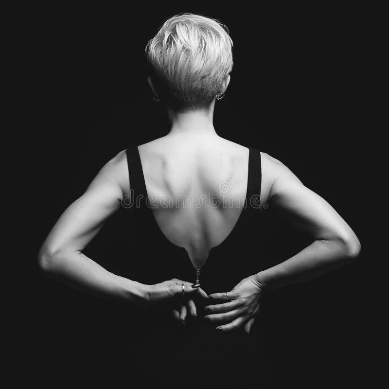 Mooie rug van jonge vrouw in een zwarte sexy kleding royalty-vrije stock afbeelding