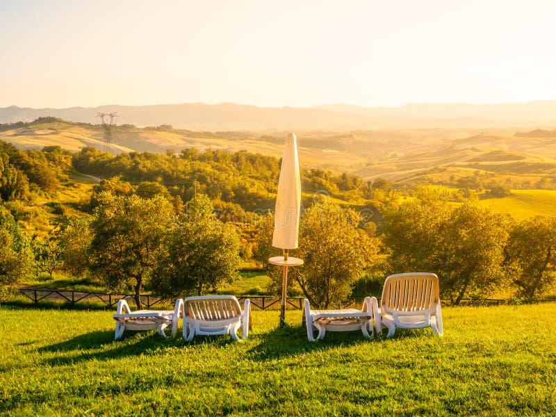 Mooie rust plaats met paraplu's en sunbeds in Toscaans landschap De zonsondergang van de avondzomer Italië royalty-vrije stock afbeeldingen