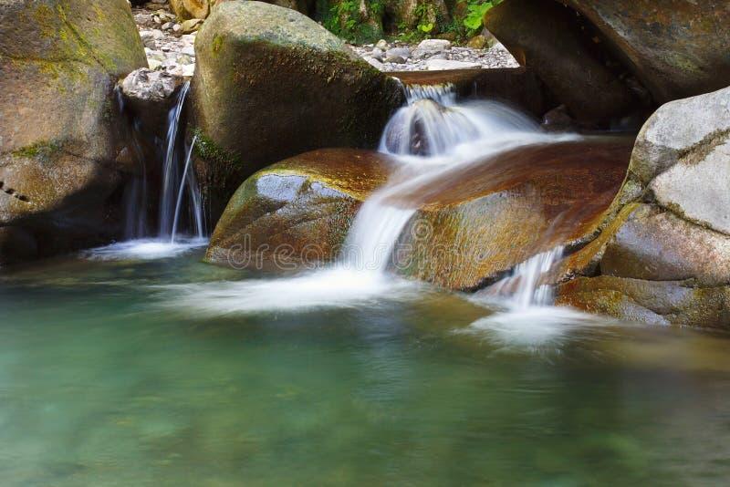 Mooie rustige waterval onder de rotsen van bergkreek royalty-vrije stock afbeeldingen