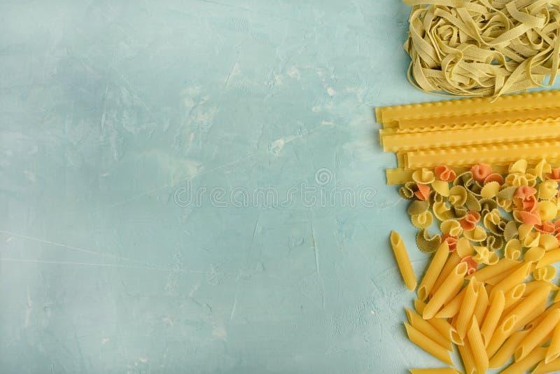 Mooie samenstelling van deegwaren met ruimte voor tekst Penne, Mafalde, Tagliatelle, Spaghetti op een blauwe achtergrond wordt op stock foto's