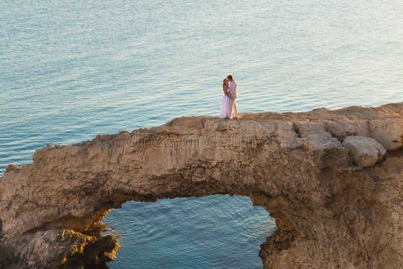Mooie schitterende bruid en modieuze bruidegom op rotsen, op de achtergrond van een overzees, huwelijksceremonie op Cyprus royalty-vrije stock afbeelding