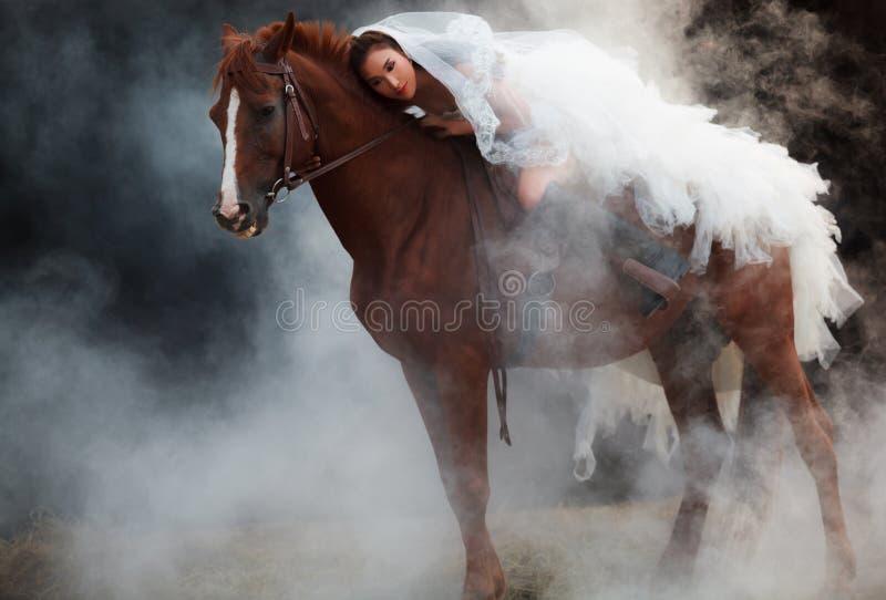 Mooie schoonheidsbruid in kostuum die van het manier het witte bruids huwelijk op sterk spierpaard op zwarte dromerige achtergron stock foto's