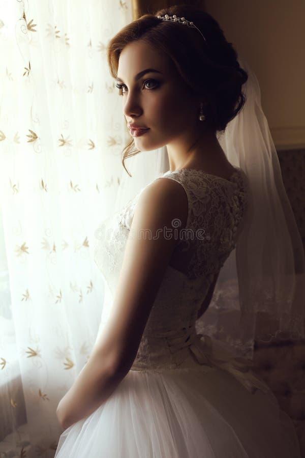 Mooie sensuele bruid met donker haar in de luxueuze kleding van het kanthuwelijk royalty-vrije stock foto