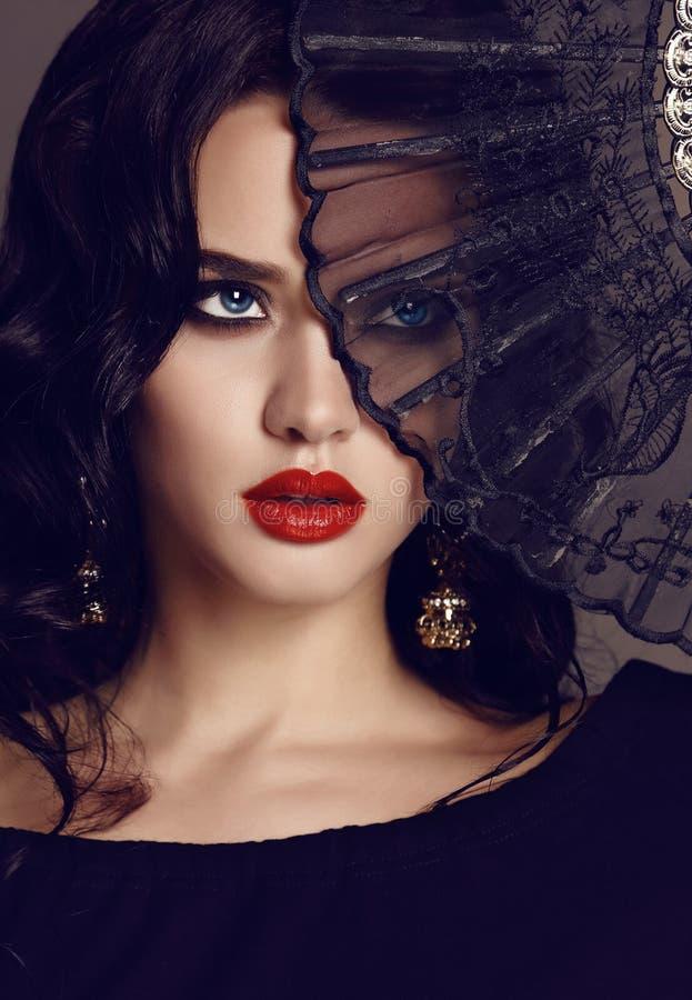 Mooie sensuele vrouw die met donker haar zwarte kantventilator in hand houden royalty-vrije stock foto's