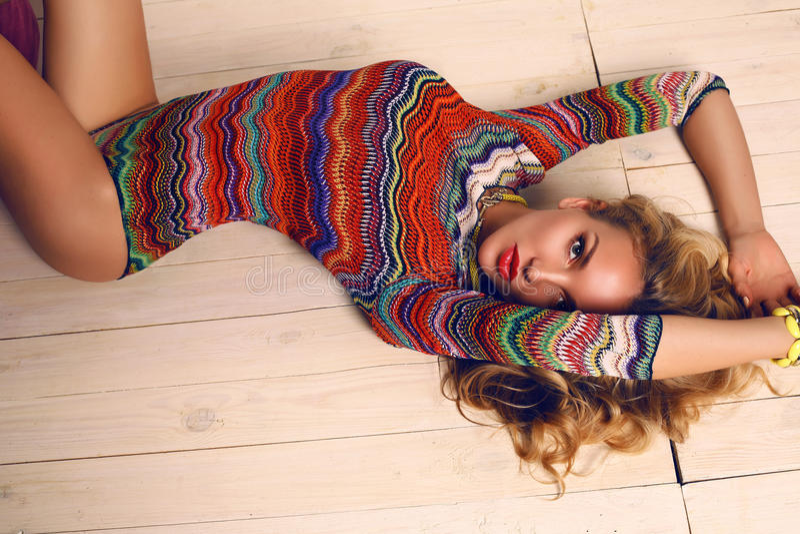 Mooie sensuele vrouw met blond krullend haar in kleurrijk kostuum stock foto's