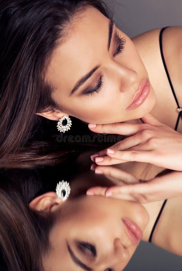 Mooie sensuele vrouw met donkere haar en avondmake-up, met juweel, stock foto