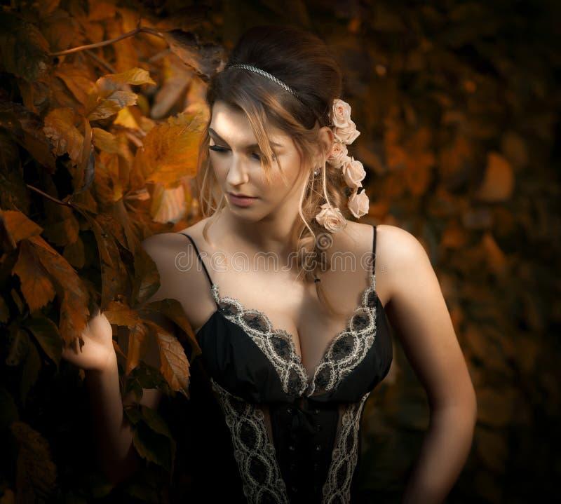 Mooie sensuele vrouw met rozen in haar het stellen dichtbij een muur van groene bladeren Jong wijfje in zwart elegant kledingsdag royalty-vrije stock afbeelding