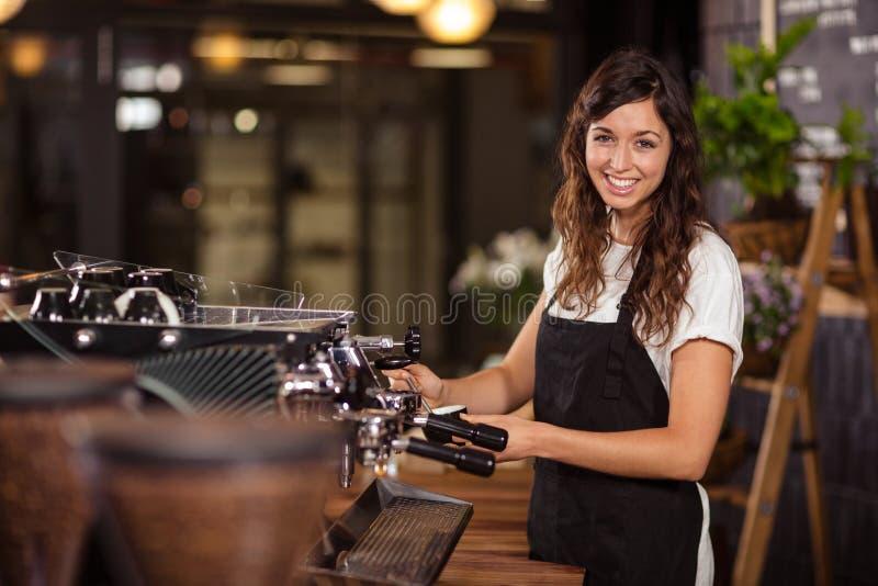 Mooie serveerster die de koffiemachine met behulp van royalty-vrije stock afbeeldingen