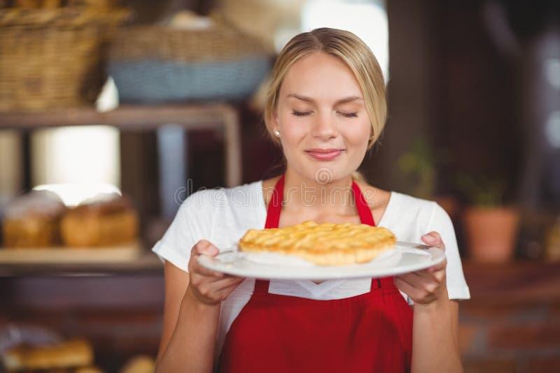 Mooie serveerster die een plaat van cake ruiken stock afbeeldingen