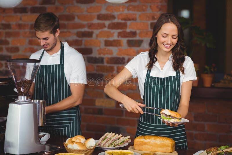 Mooie serveerster die een sandwich plukken stock afbeeldingen