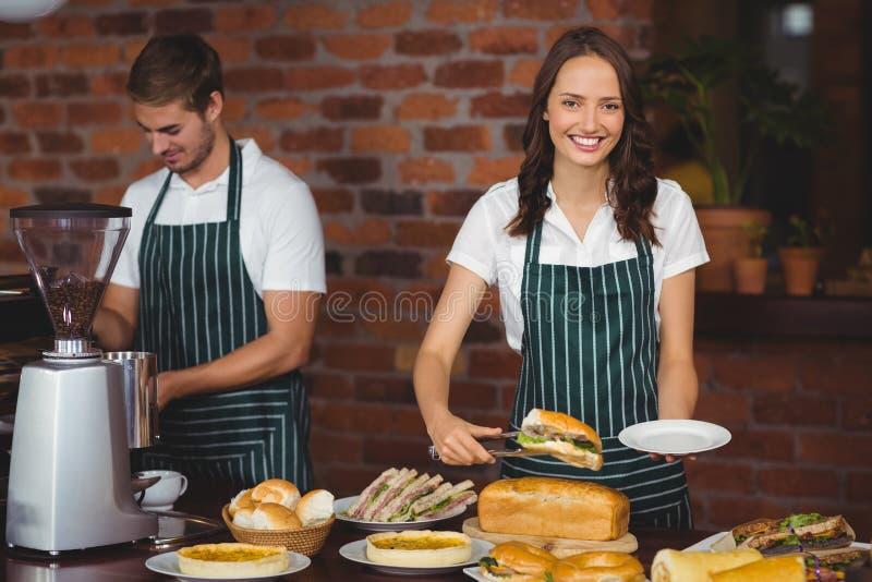 Mooie serveerster die een sandwich plukken stock afbeelding