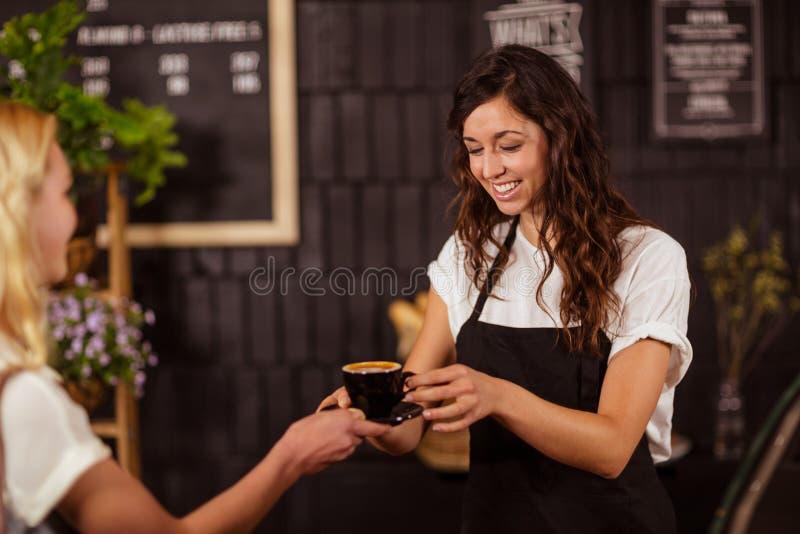 Mooie serveerster die kop van koffie aanbieden aan klant royalty-vrije stock fotografie