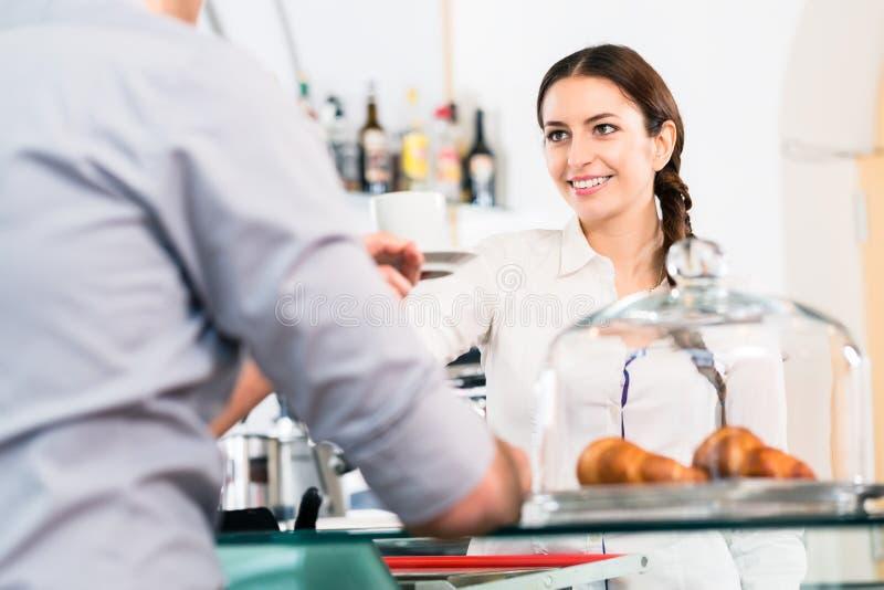 Mooie serveerster die mannelijke klant met een kop van koffie FO dienen stock foto