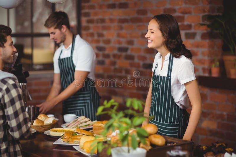 Mooie serveerster die met een klant spreken stock foto's