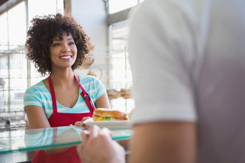 Mooie serveerster die sandwich geven aan klant royalty-vrije stock fotografie