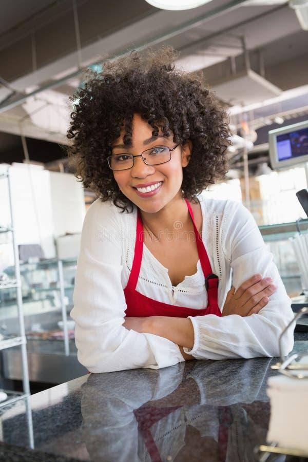 Mooie serveerster met glazen die op teller leunen stock fotografie