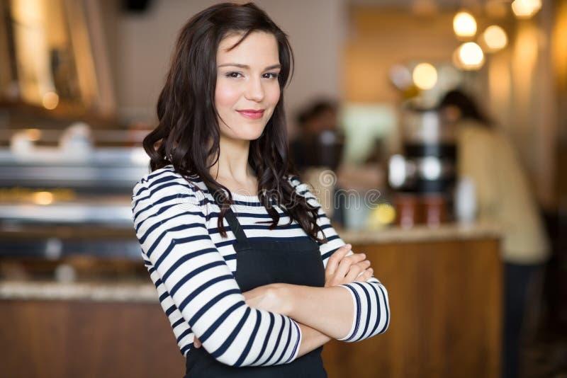 Mooie Serveerster Standing Arms Crossed in Cafetaria royalty-vrije stock foto's