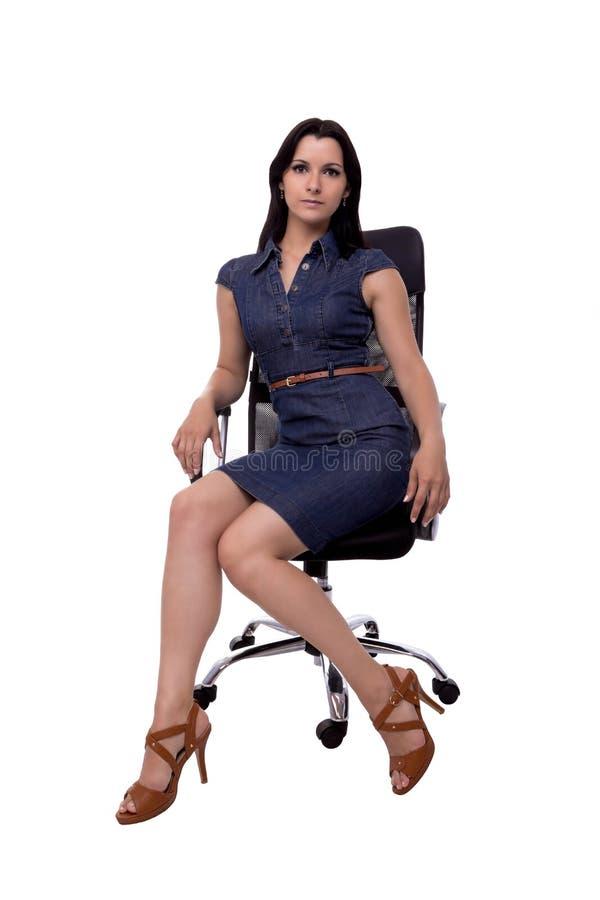 Mooie, sexy bedrijfsdievrouwenzitting als bureauvoorzitter op een witte achtergrond wordt geïsoleerd royalty-vrije stock afbeeldingen