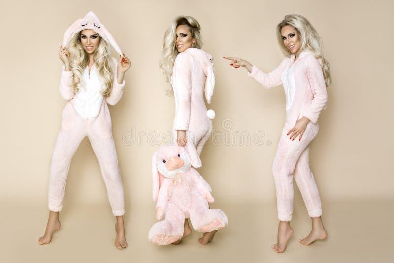 Mooie sexy blondevrouw die een pyjama, een konijntjeskostuum dragen, die gelukkig glimlachen stock foto's