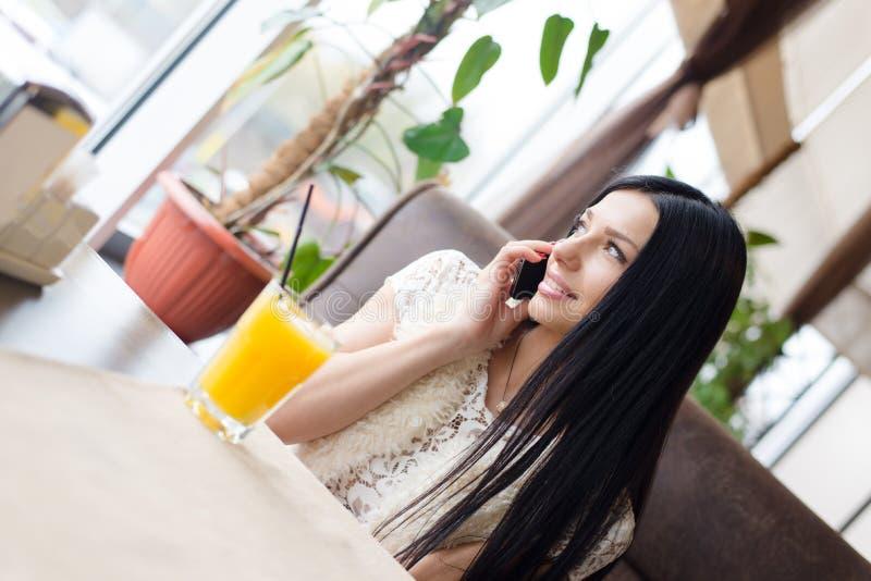 Mooie sexy donkerbruin meisjes jonge vrouw die pret hebben die op de mobiele zitting van de celtelefoon in koffiewinkel of restau stock foto