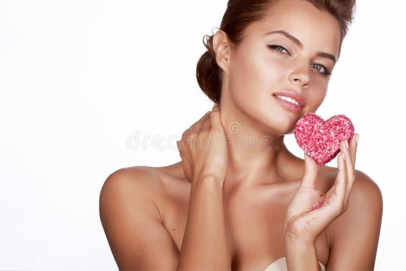Mooie sexy donkerbruine vrouw die cakevorm van hartromanti eten royalty-vrije stock foto's