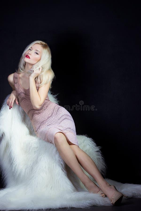 Mooie sexy elegante opvallend het blondemeisje met heldere make-up in roze kleding in de Studio op een zwarte zitting als achterg royalty-vrije stock afbeelding