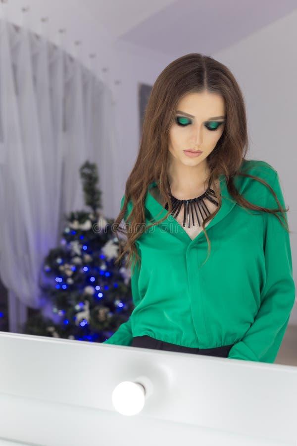 mooie sexy elegante vrouw met heldere avondsamenstelling in schaduwen van groen met lang haar in een groene avondjurk in feesteli stock fotografie