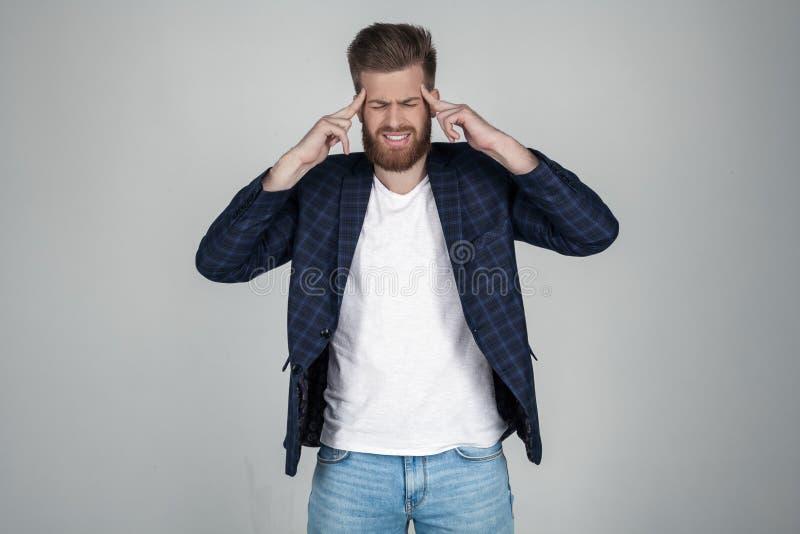 Mooie sexy gebaarde mens met een mooie haarstijl houdt zijn hoofd met beide handen Hij heeft een hoofdpijn Problemen op het werk royalty-vrije stock afbeeldingen