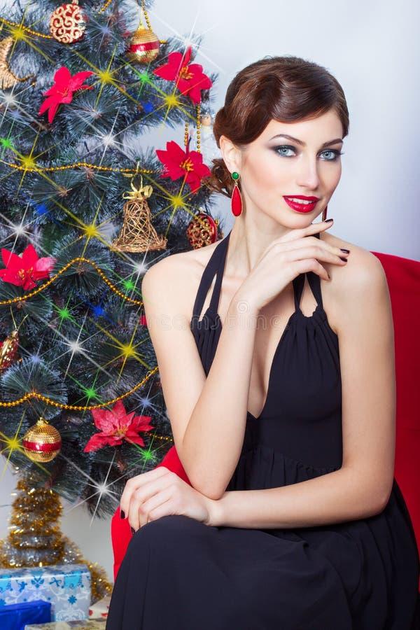 Mooie sexy gelukkige glimlachende jonge vrouw in avondjurk met heldere make-up met rode lippenstiftzitting dichtbij de Kerstboom stock afbeeldingen