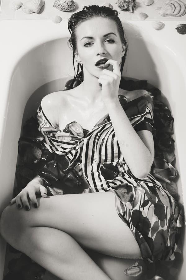 Mooie sexy jonge vrouw die bad met bloembloemblaadjes hebben stock afbeeldingen