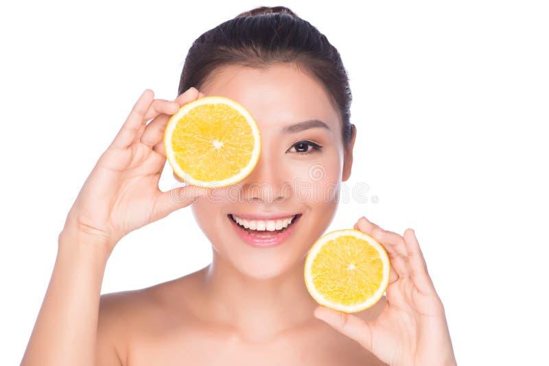 Mooie sexy jonge vrouw die met perfecte gezonde huid en lange bruine de make-up naakte schouders van de haardag oranje citroengra stock fotografie