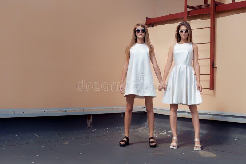 Mooie sexy jonge vrouw twee in het modieuze witte kleding stellen op een dak met zonnebril in de heldere de zomerdag royalty-vrije stock afbeelding