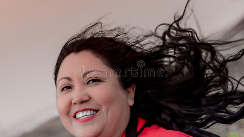 Mooie sexy Latijnse Mexicaanse vrouw met lang zwart die haar door de wind wordt verfomfaaid royalty-vrije stock foto
