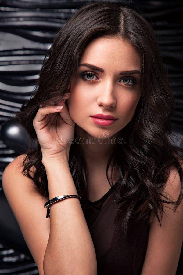 Mooie sexy make-upvrouw die met roze lippenstift, contrastwenkbrauw en lang krullend haar haar grote romantische blauwe ogen kijk stock foto