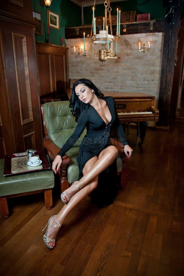 Mooie sexy meisjeszitting op stoel en het ontspannen Portret van donkerbruine vrouw met lange benen die uitdaging vormen Sensueel royalty-vrije stock afbeeldingen